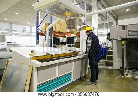 Back Of Male Technician Operating Milling Machine At Control Panel. Middle Aged Man In Hardhat Worki