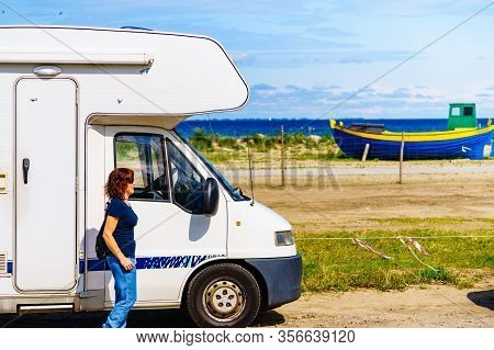 Travel Holidays In Motorhome. Mature Woman Tourist At Camper Car On Sea Coast.