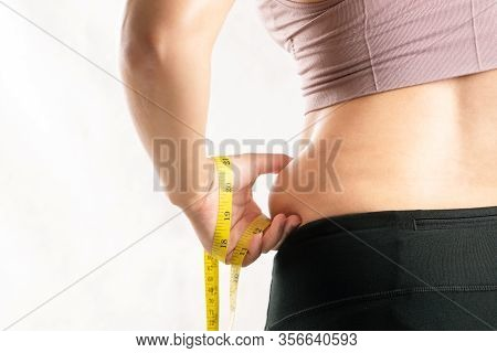 Fat Woman, Fat Belly, Chubby, Obese Woman Hand Pinching On Her Excessive Belly Fat Waist With Measur