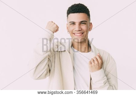 Happy Young Man Shaking Fists. Cheerful Handsome Young Man Triumphing And Smiling At Camera On Grey