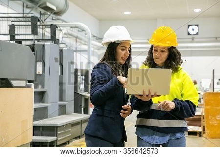 Concentrated Women Looking At Laptop At Manufacturing Plant. Two Female Employees Talking While Stan