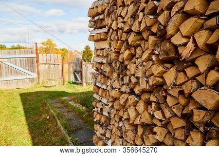 Woodpile Of Firewood Outdoors In Summer Day. Tacked Chopped Logs. Heap Firewood. Chopped Firewood Is