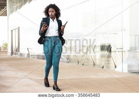 Serious Female Employee Walking Outside With Cell. Young African American Business Woman Using Mobil
