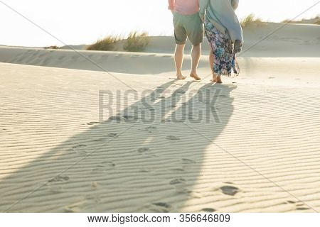 Cropped Shot Of Young Couple Strolling On Sandy Beach. Legs Of Husband And Wife Strolling On Seashor
