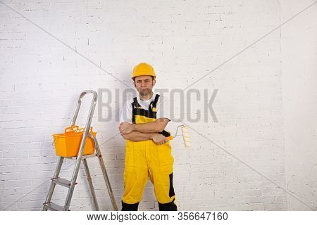 A Construction Worker Specializing In Painter Work. He Is Dressed In Work Clothes And A Helmet And I