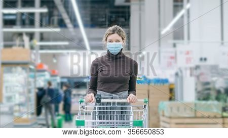 A Woman In A Medical Mask Stands In A Supermarket With A Timelapse Grocery Cart. Protection From Cor