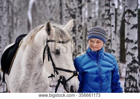 Young Pretty Woman In A Blue Jacket And A Sports Hat For A Walk With A White Horse In The Winter Bir