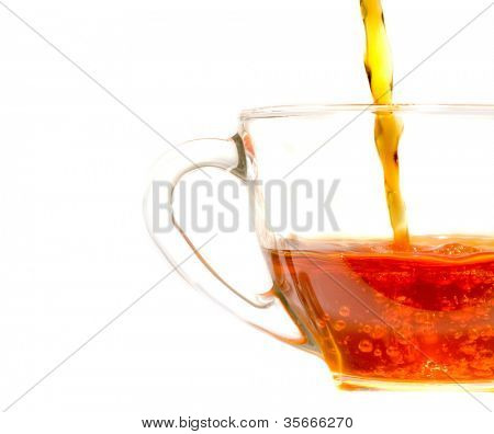 Pouring  tea into a clear glass cafe style cup and saucer
