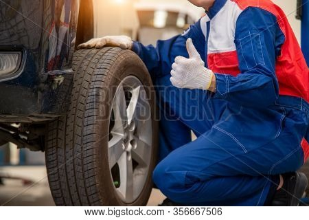 Auto Mechanic Changing Tire Outside,car Service.hands Replace Tires On Wheels.tire Installation Conc