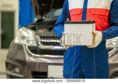 Mechanic Working On Car In His Shop,portrait Of Confident Auto Mechanic With Car Battery In Workshop