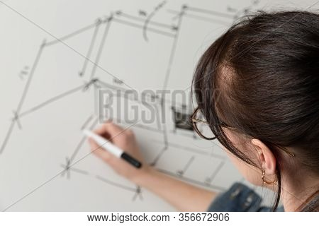 Close-up Of A Young Female Architect Drawing A Sketch For A New Famaly Home Project. Concept Of Work