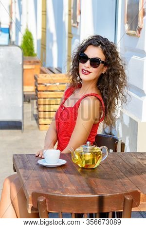 Happy smiling girl is sitting at a table in a caf?. Sunny summer day.