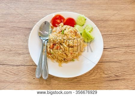Fried Rice Placed On A Wooden Table With Cucumbers And Tomato