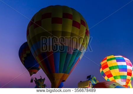 Colorful Hot Air Balloons Flying Above The Ground At The Food And Drink Festival In Night Time.