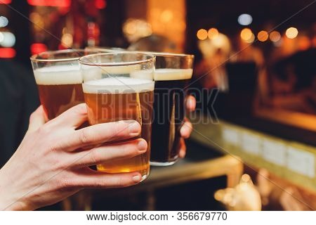 Friends Cheering With Beer Glasses Sitting Around Cafe Bar Table - Group Of Multiracial People Toast