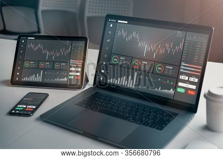 Stock Exchange Market Concept, Laptop And Tablet, Smartphone On The Table With Graphs Analysis Candl