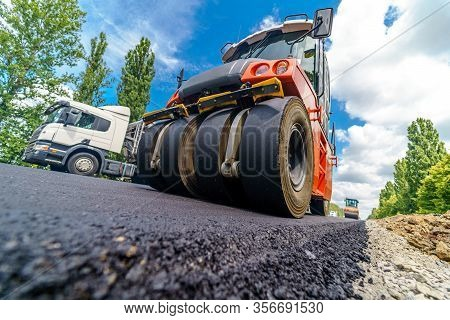 Road Repair, Compactor Lays Asphalt. Heavy Special Machines. Asphalt Paver In Operation. Side View.