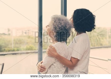 Peaceful Middle Aged And Senior Women Watching Scene From Window. Adult Daughter Embracing Old Mothe