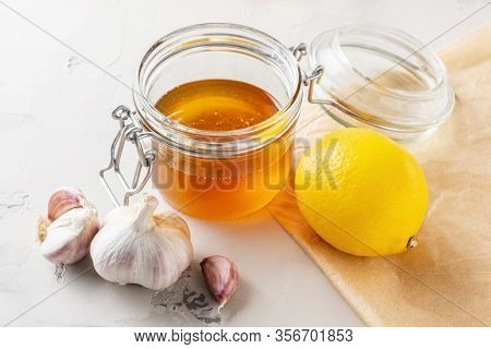 Alternative Medicine, Natural Home Remedy For Cold And Flu. Glass Jar With Honey, Lemon And Garlic O