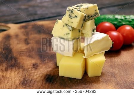 Assortment Of Different Cheese Type On A Wooden Board. Different Pieces Of Cheese, Blue Cheese, Mold