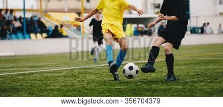 Running Soccer Players In Duel. Youth Athletes Kicking Black And White Football Ball. Junior Youth S