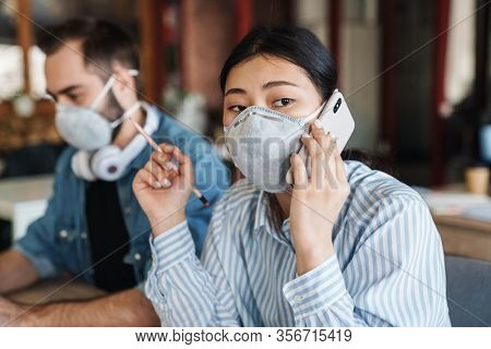 Photo of multinational young students in medical masks talking on cellphone while studying at classroom