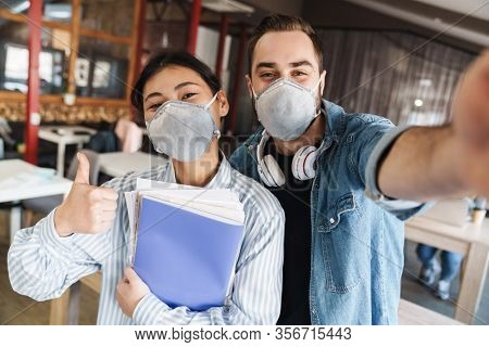Photo of multinational joyful students in medical masks taking selfie photo and showing thumb up at classroom
