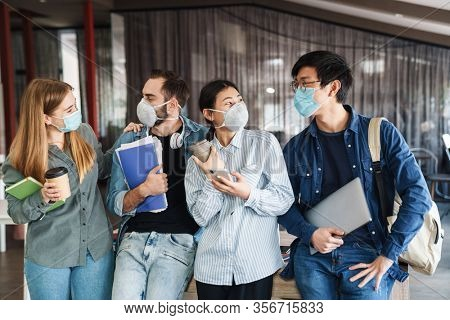 Photo of multinational joyful students in medical masks talking while standing at classroom