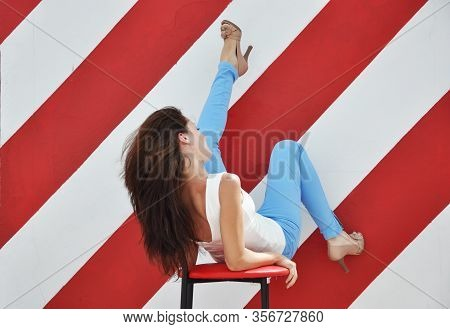 Woman In High Heels Sit On Chair, Studio Shot. Sexy Woman Sit On Bar Chair. Happy Girl Relax On Fash