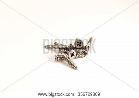 Pile Of Metal Phillips Screws On A Background On White