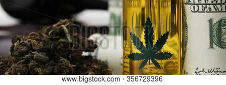 Close-up View Of Plastic Bottle With Cannabinoid Extract And Dry Marijuana. Rolled Banknotes With Wo