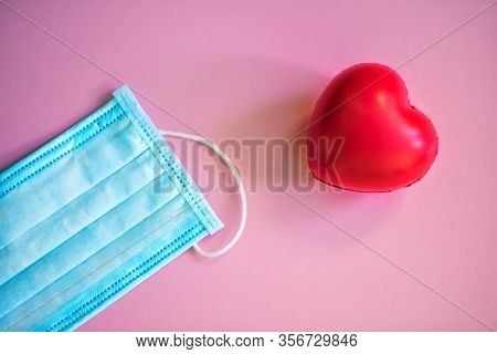 Medical Face Mask And Red Heart. Medical Protective Mask On Pink Background With Red Heart Nearby. D