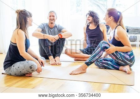 Cheerful Young People In Yoga Studio. Happy Men And Women In Sportswear Sitting On Yoga Mats, Talkin