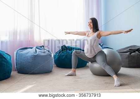 Beautiful European Woman Doing Pregnant Exercises. Expectant Mother Is Doing Exercises With A Fitnes