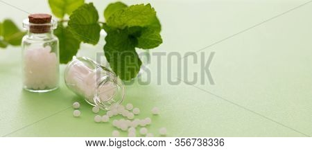 Homeopathy, Globules Scattered Out Of Glass Bottle, Green Background