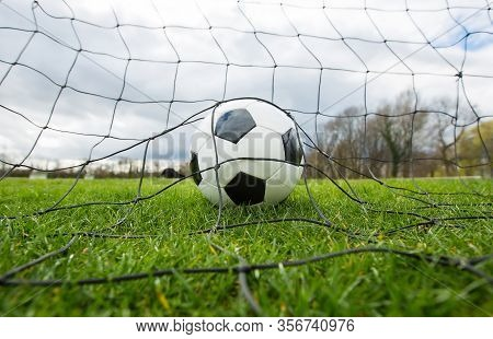 Close Up Of A Soccer Ball Behind The Gates Net, Goal Scoring Concept. Outdoors Football Match, Pract