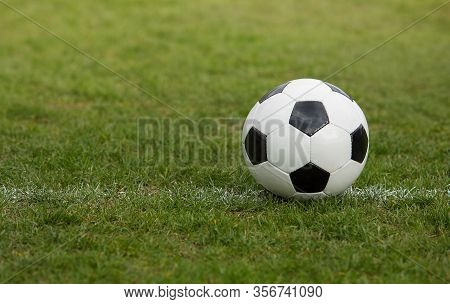 Classic Soccer Ball, Typical Black And White Pattern, Placed On The White Marking Line Of The Stadiu
