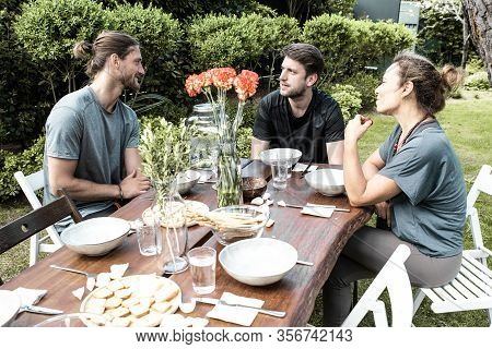 Smiling People Talking In Backyard. Cheerful Young Male And Female Friends Sitting At Table With Org
