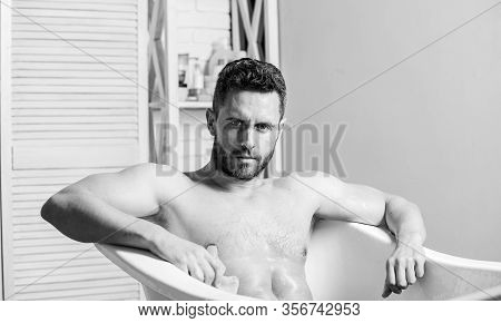 Macho Naked In Bathtub. Wash Off Foam With Water Carefully. Sex And Relaxation Concept. Macho Attrac