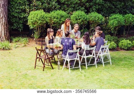Friends In Sportswear Eating Outdoors. Sporty Young Male And Female Friends Gathering Around Table A