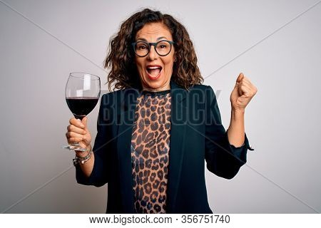 Middle age brunette woman drinking glass of red wine over isolated white background screaming proud and celebrating victory and success very excited, cheering emotion