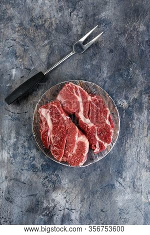 Two Fresh Raw Meat Prime Black Angus Chuck Roll Steak On A Wooden Cutting Board On A Gray Background