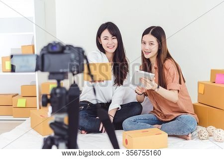 Two Asian Women Using Digital Video Camera For Recording And Presenting New Product Advertisement. V