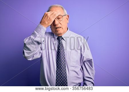 Grey haired senior business man wearing glasses standing over purple isolated background tired rubbing nose and eyes feeling fatigue and headache. Stress and frustration concept.