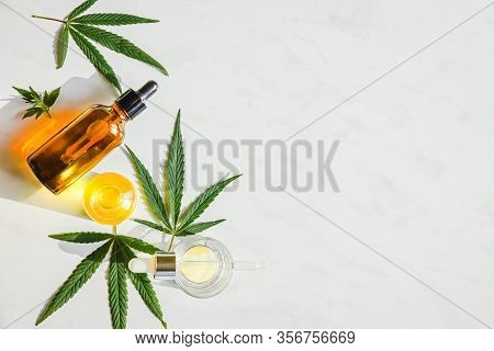 Glass Brown Bottle With Cannabis Cbd Oil And Marijuana Leaves On A Marble Background. Copy Space