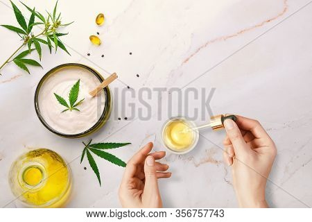 Pipette With Cbd Cosmetic Oil In Female Hands On A Table Background With Cosmetics, Cream With Canna