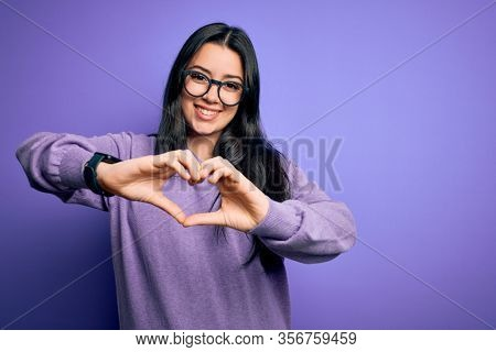 Young brunette woman wearing glasses over purple isolated background smiling in love doing heart symbol shape with hands. Romantic concept.