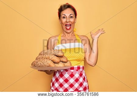 Middle age senior housewife pin up woman wearing 50s style retro dress cooking wholemeal bread very happy and excited, winner expression celebrating victory screaming with big smile and raised hands