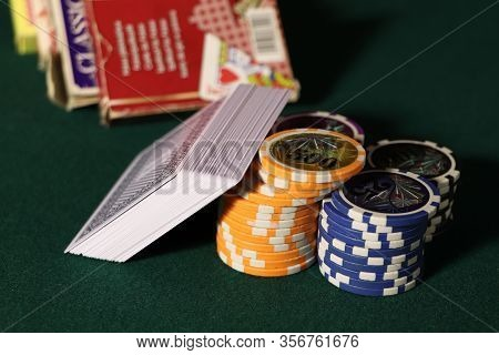 Playing Cards And Poker Chips On Agreen Table. Stack Of Chips For Poker.