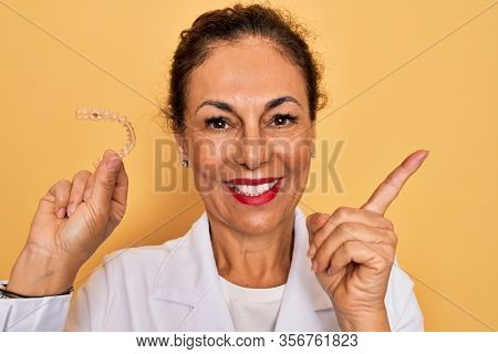 Middle age senior dentist woman holding clear aligner for teeth correction very happy pointing with hand and finger to the side